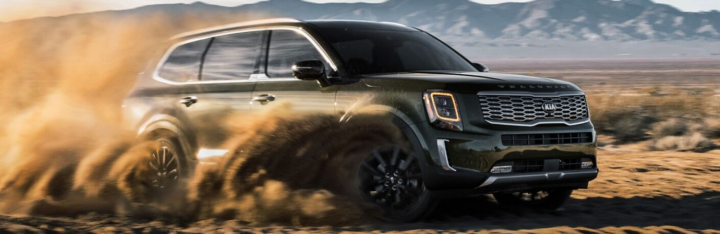 Exterior view of a green 2020 Kia Telluride spitting up sand while driving through the desert