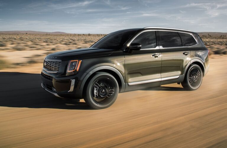 Exterior view of the front of a green 2020 Kia Telluride driving through the desert