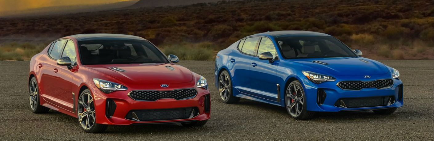 Red and Blue 2021 Kia Stinger Models on a Desert Road