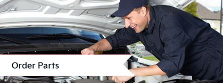 man smiling and working under car hood