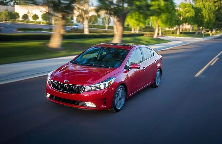 red 2017 Kia Forte driving through residential neighborhood