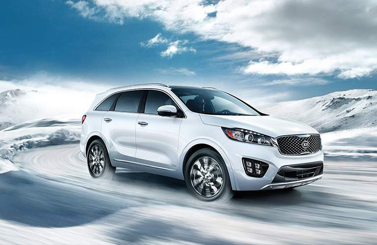 2018 Kia Sorento driving around a curve on a road with snowy hills in the background