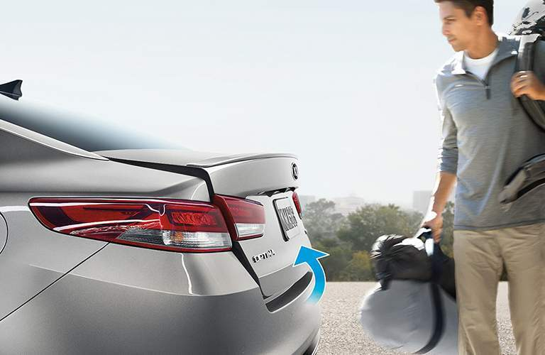 Man carrying multiple bags opening the trunk of the 2018 Kia Optima