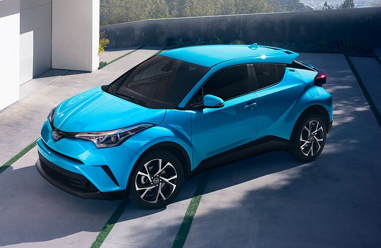 bright blue 2019 Toyota C-HR parked outside modern home