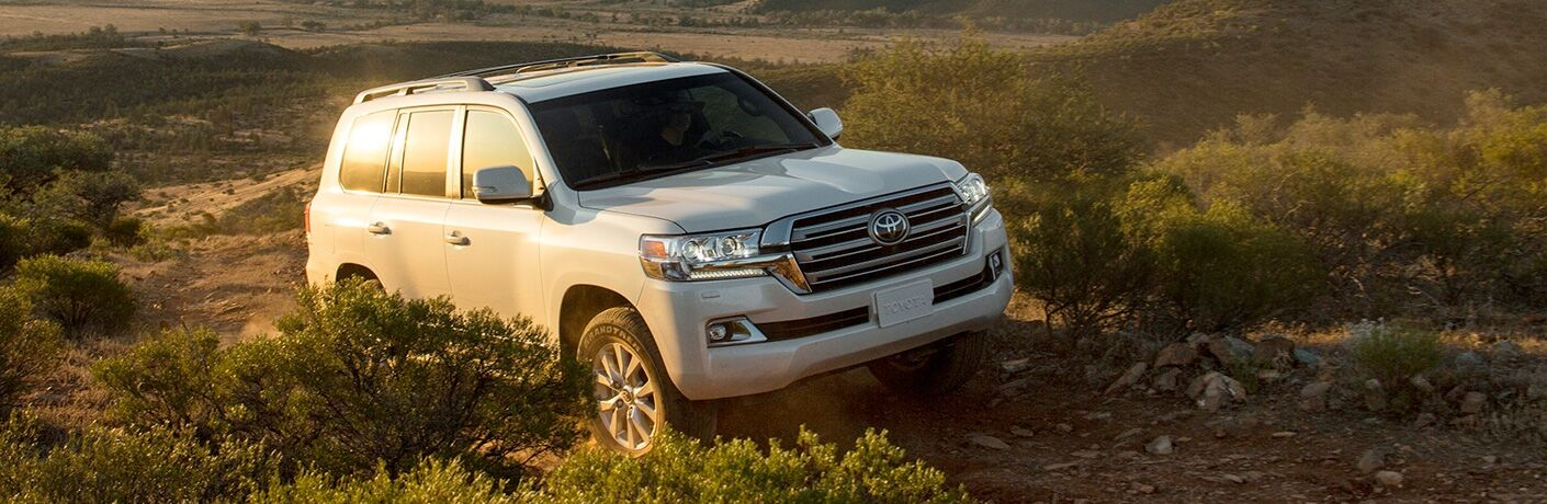 White 2019 Toyota Land Cruiser driving on a rocky trail
