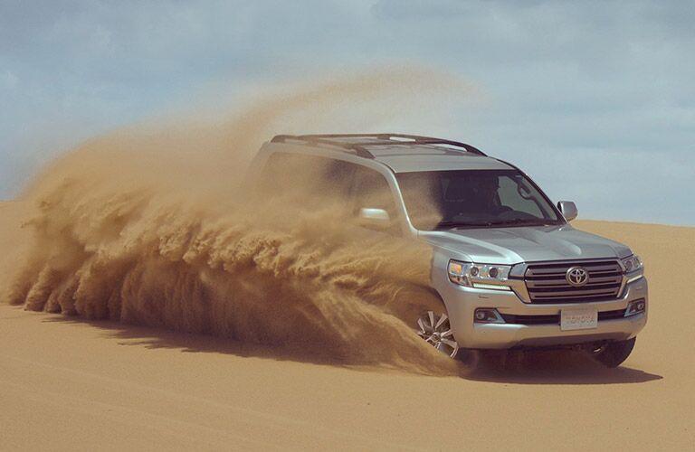 Silver 2019 Toyota Land Cruiser driving on sandy terrain