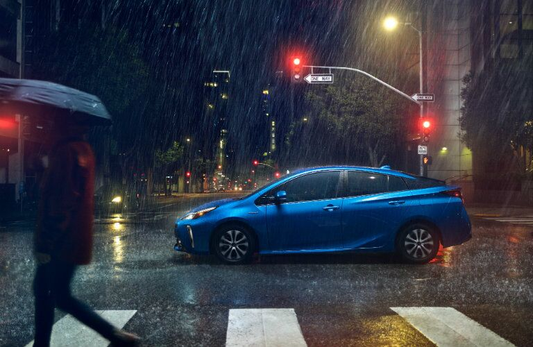 side profile of blue 2019 Toyota Prius driving through intersection in the rain