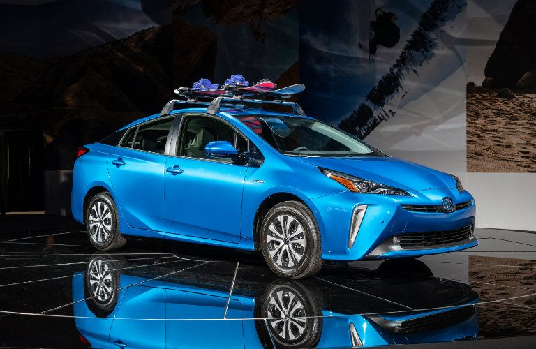 blue 2019 Toyota Prius carrying snowboarding equipment parked on stage