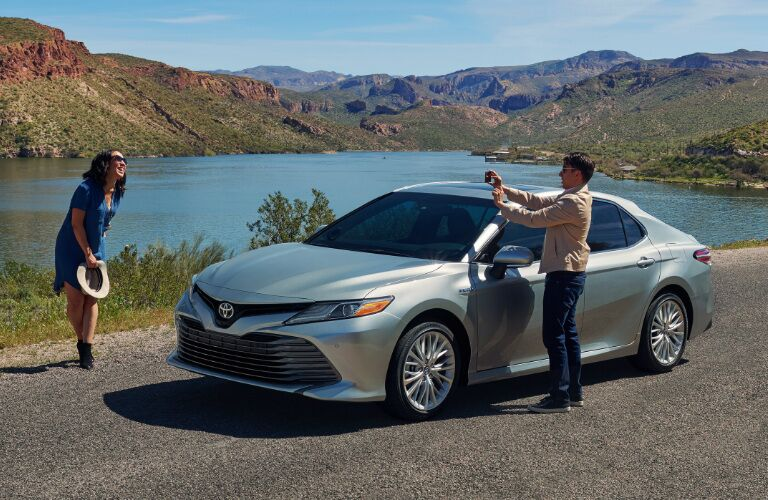 A man taking a photo of a woman next to a silver 2019 Toyota Camry Hybrid
