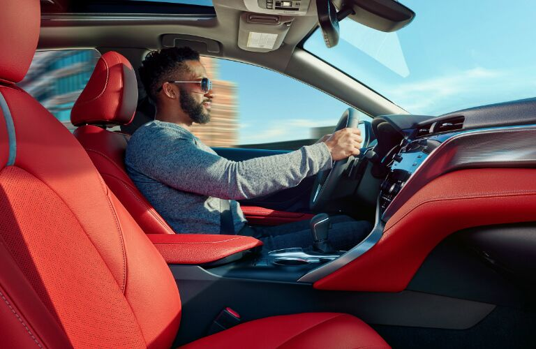 A bearded man driving a 2019 Toyota Camry Hybrid