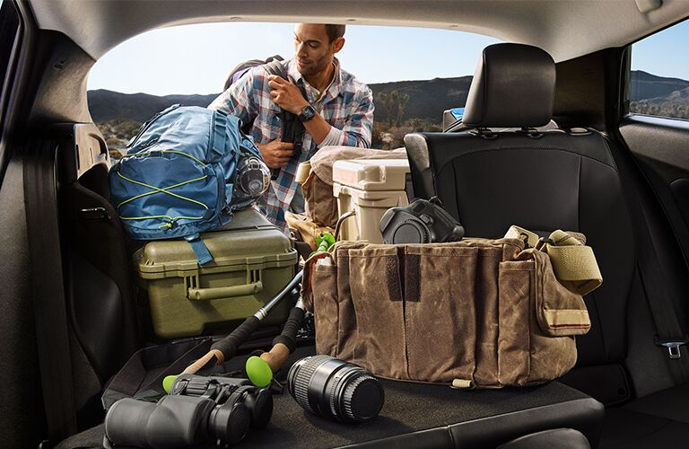 A man getting gear from the cargo area of a 2020 Toyota Prius