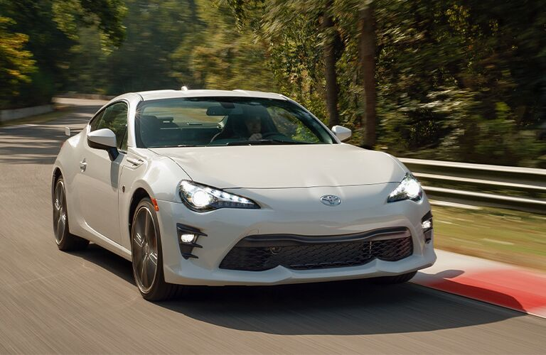 White 2020 Toyota 86 driving by a forest
