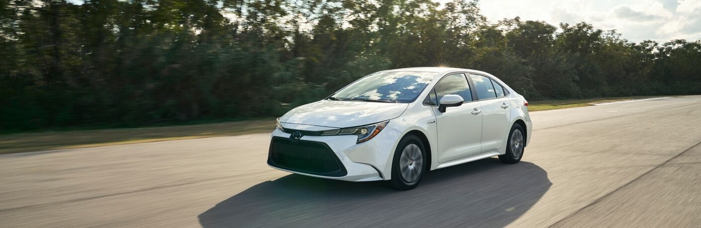 side view of white 2020 Toyota Corolla driving on road