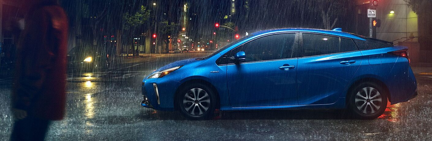 Blue 2020 Toyota Prius driving on a rainy street