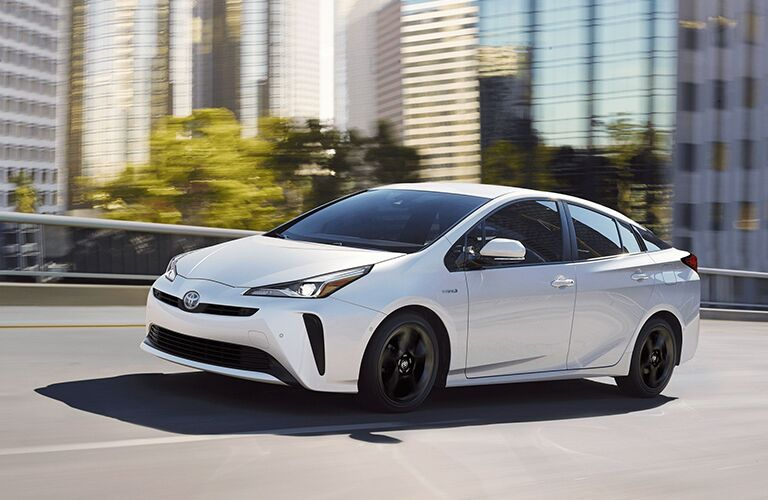 White 2020 Toyota Prius driving by tall buildings