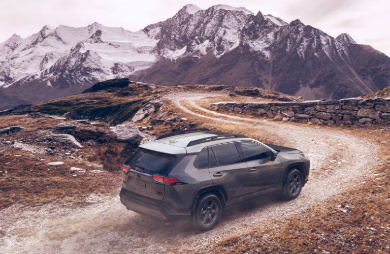 gray 2020 Toyota RAV4 TRD Off-Road driving on trail toward mountains