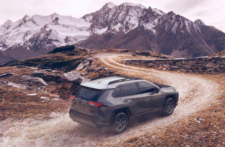 gray 2020 Toyota RAV4 TRD Off-Road driving on trail toward mountains