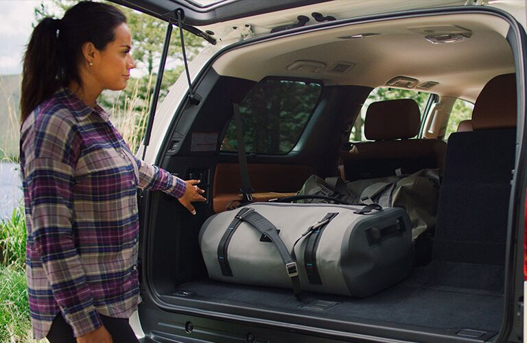 A woman standing next to the cargo area of a 2020 Toyota Sequoia