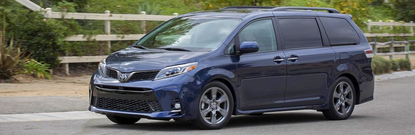Blue 2020 Toyota Sienna driving by a wood fence