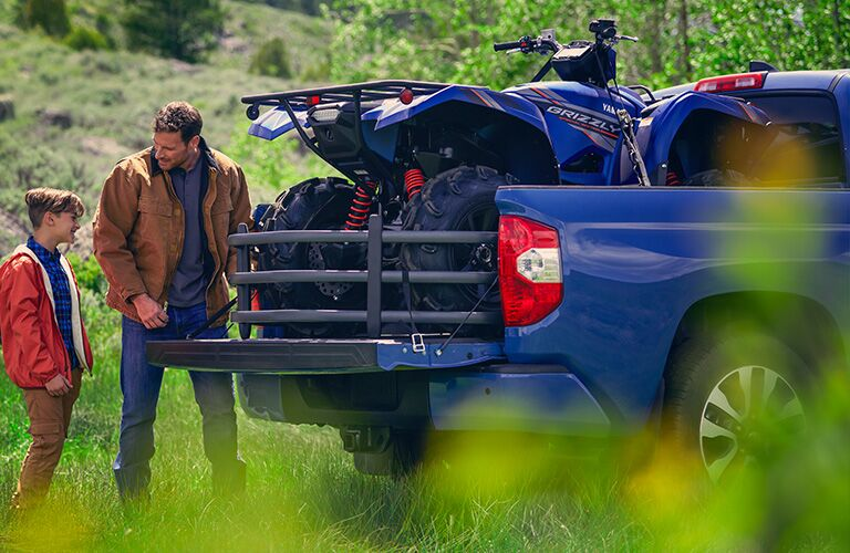 A man and a boy standing next to a blue 2020 Toyota Tundra with an ATV in the pickup bed