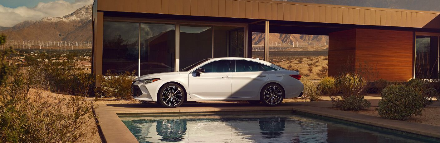 White 2020 Toyota Avalon Hybrid parked next to a swimming pool