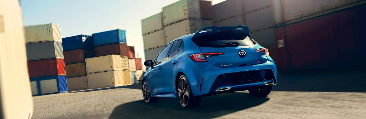 Blue 2020 Toyota Corolla Hatchback driving by some shipping containers