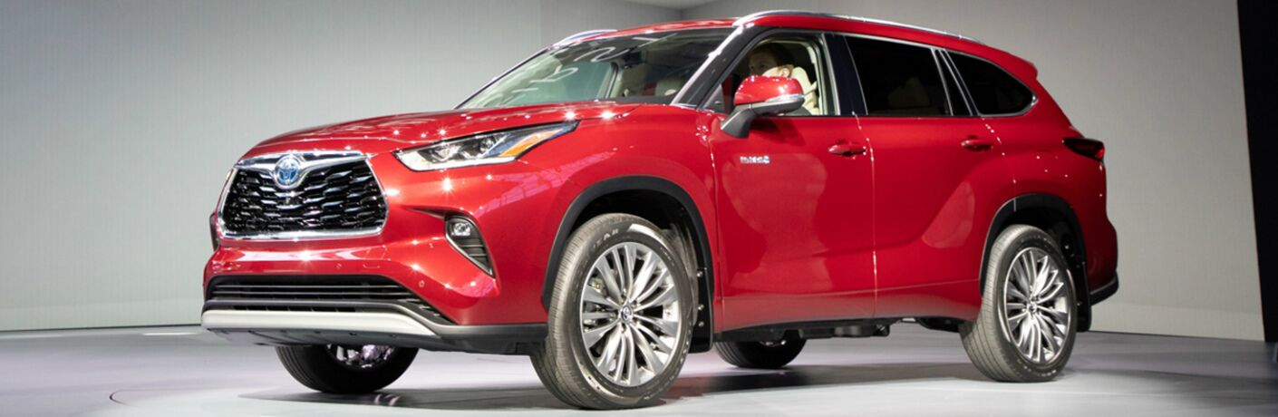 Driver's side front angle view of red 2020 Toyota Highlander Hybrid