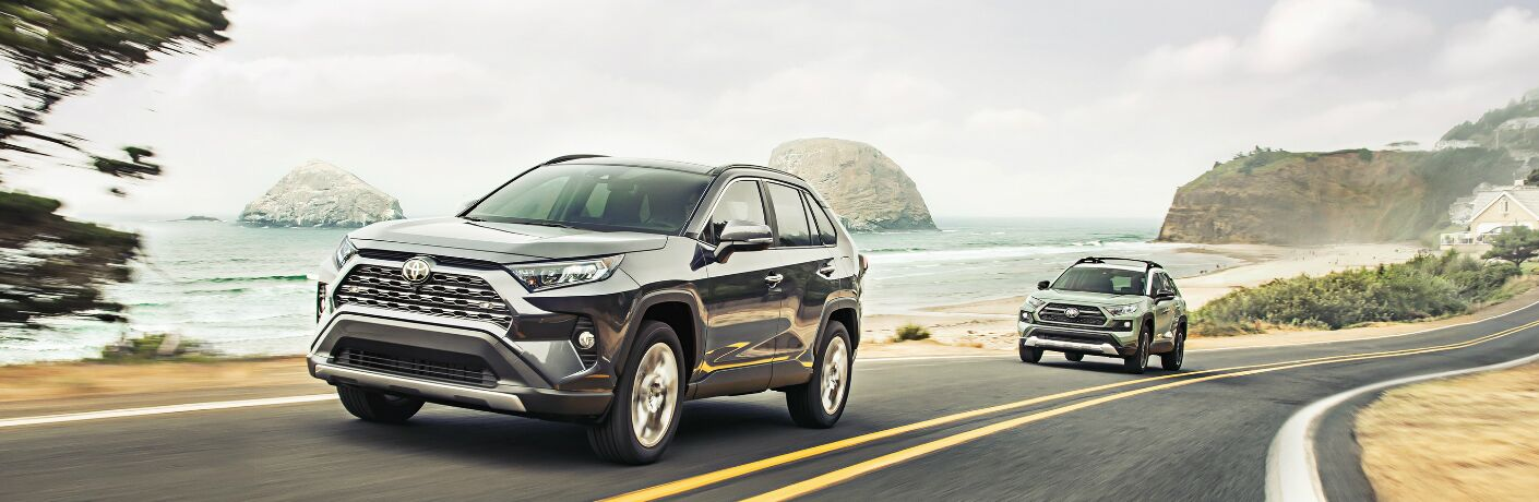 Two 2020 Toyota RAV4 vehicles driving on a coastal road