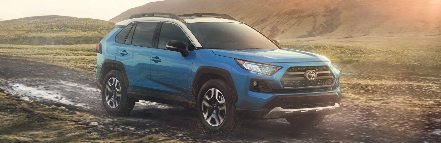 Blue 2020 Toyota RAV4 Hybrid driving on a muddy road