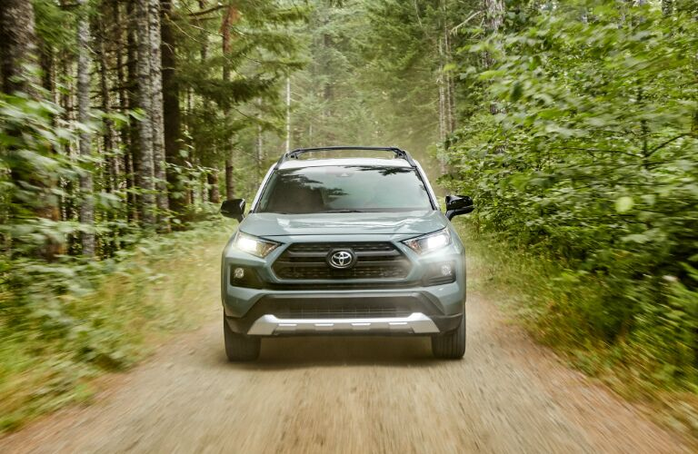 Light green 2020 Toyota RAV4 Hybrid driving through a forest