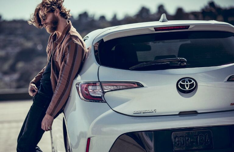 A bearded man leaning up against a white 2020 Toyota Corolla Hatchback