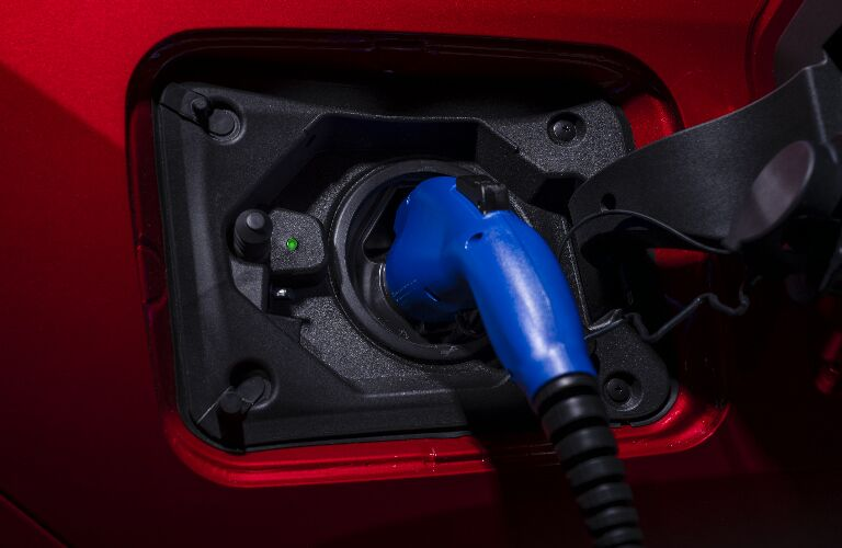 A charger plugged into a red 2021 Toyota RAV4 Prime