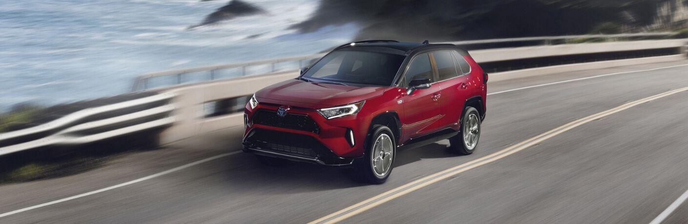Red 2021 Toyota RAV4 Prime driving on a coastal road