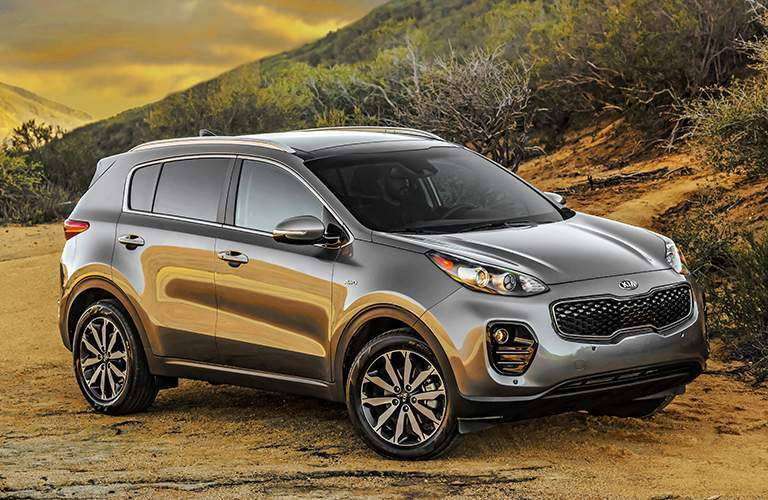 2018 Kia Sportage in front of a brush hill