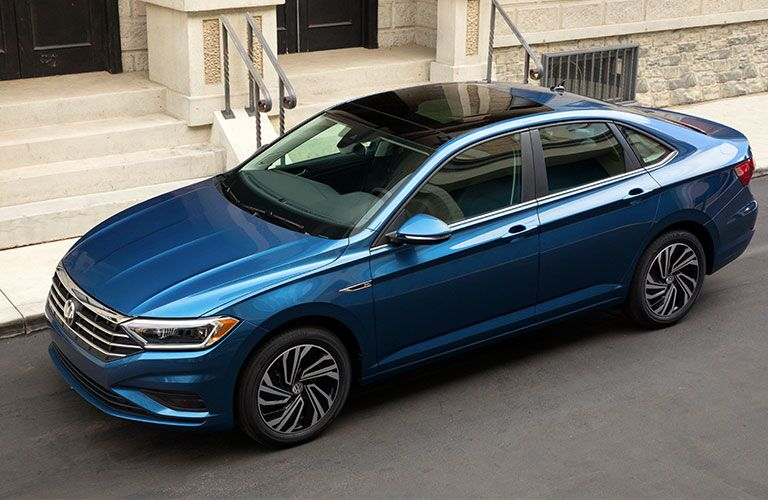 Exterior view of a blue 2019 Volkswagen Jetta parked outside a city building