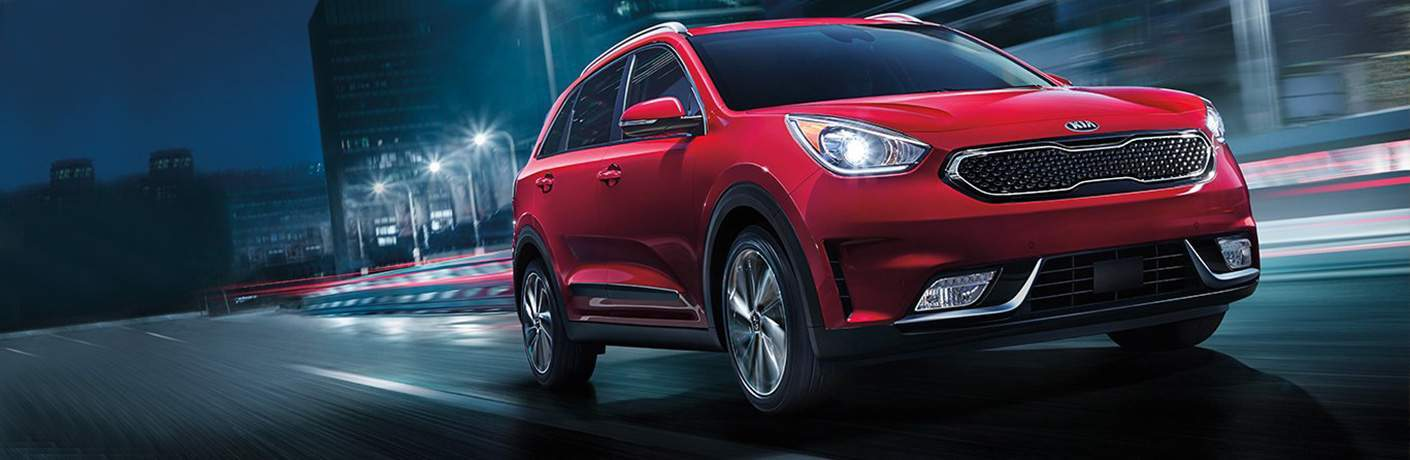 Red 2018 Kia Niro driving on city street at night with tall buildings in background
