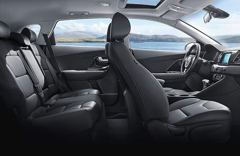 Two rows of seating inside 2018 Kia Niro with gear shifter and steering wheel prominent