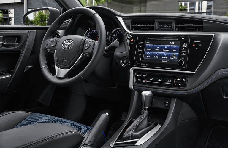 interior of 2018 toyota corolla with infotainment system dashboard steering wheel and more shown in front of building
