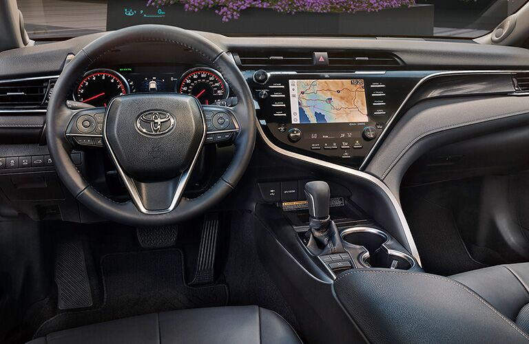 2019 Toyota Camry interior shot of front seating, steering wheel, transmission, and infotainment screen