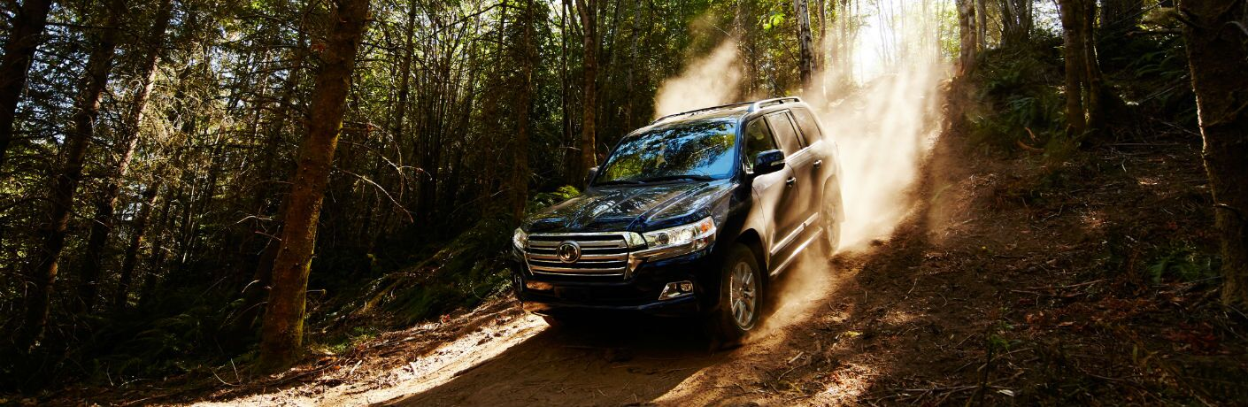 A photo of the 2018 Toyota Land Cruiser coming down a hill in the woods.