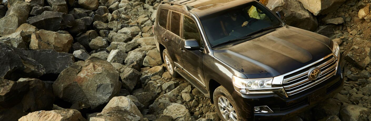 A photo of the 2018 Toyota Land Cruiser crossing a rocky path.