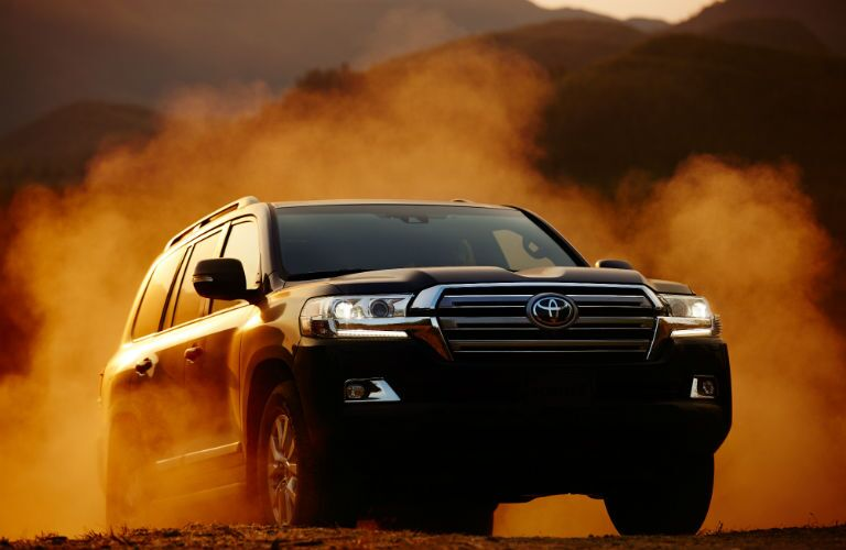 A head-on photo of the 2018 Toyota Land Cruiser crossing a dusty trail.