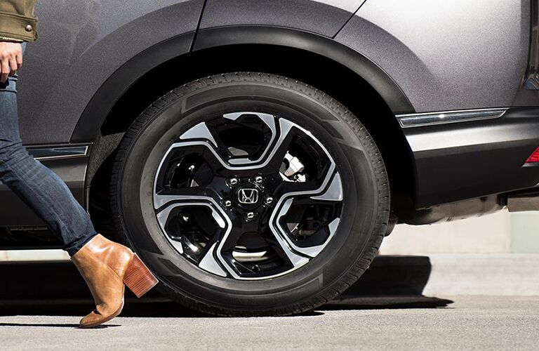 person's foot next to the wheel of a Honda CR-V