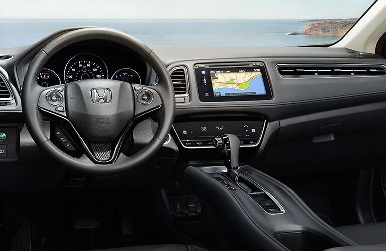 interior view of steering wheel and dashboard inside the 2018 Honda HR-V looking out to the ocean