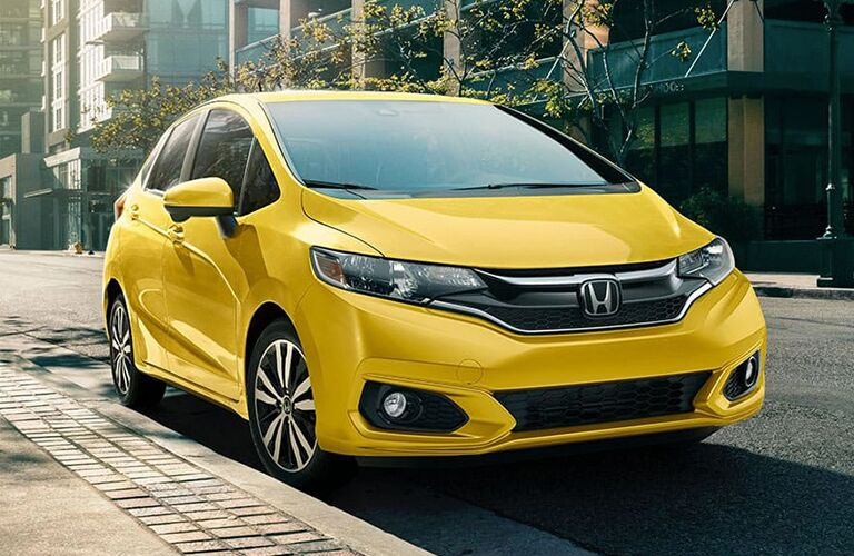 front view of yellow honda fit parked on side of road