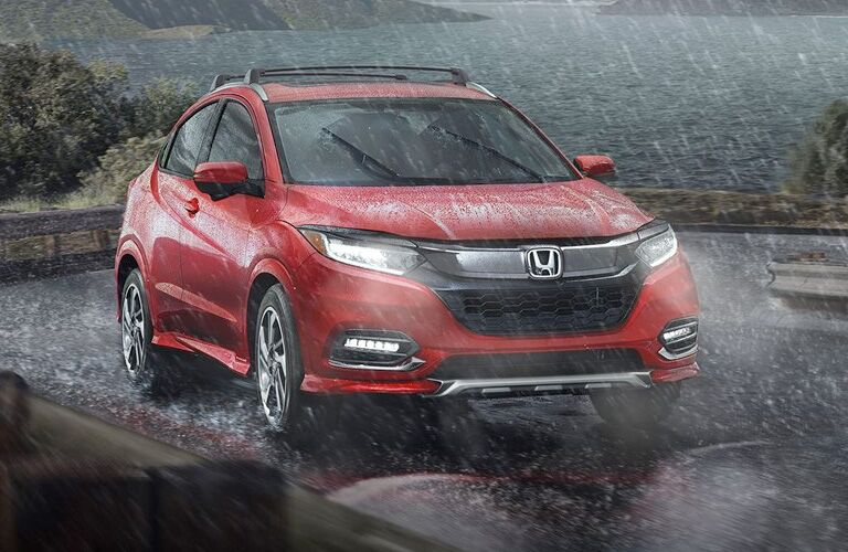 red honda hr-v driving near the ocean in the rain