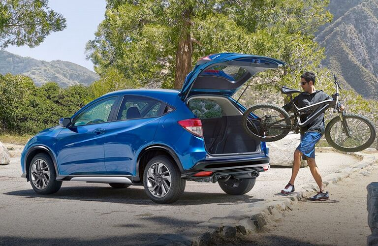 man putting bike in back of blue honda hr-v