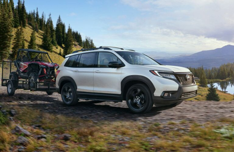 white honda passport towing an off-road vehicle
