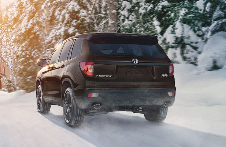 rear view of black honda passport driving in snow