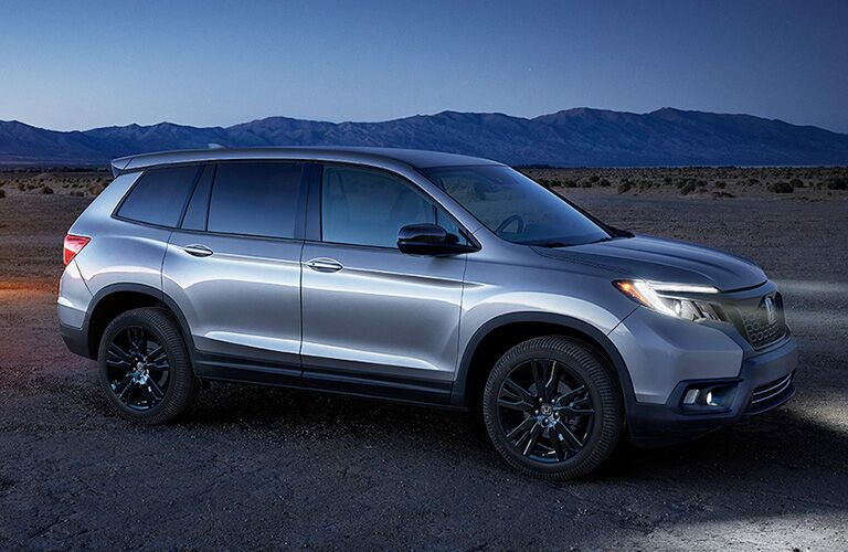 right side view of silver honda passport at night